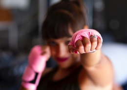 Woman punching air with hands tied for boxing gloves